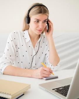 Cours en ligne avec une étudiante tenant ses écouteurs