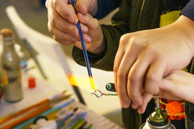 Cours de maître sur la fabrication de jouets décoratifs en verre, l'enseignant montre comment faire fondre et fabriquer. gros plan et flou
