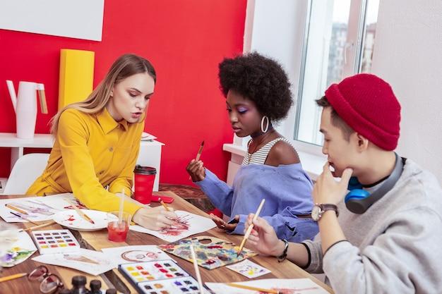 Cours de maître. jeune artiste célèbre aux cheveux blonds donnant une classe de maître à des étudiants talentueux
