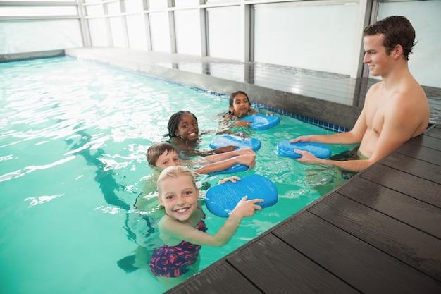 Cours de natation mignon dans la piscine avec entraîneur