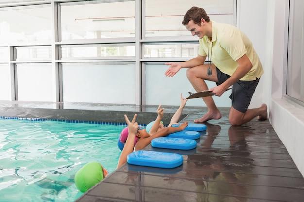 Cours de natation mignon à l'écoute de l'entraîneur