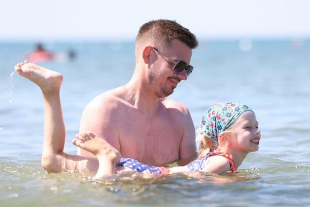 Cours de natation pour enfants sur base individuelle. l'homme à lunettes de soleil tient la fille avec ses mains au-dessus de l'eau.