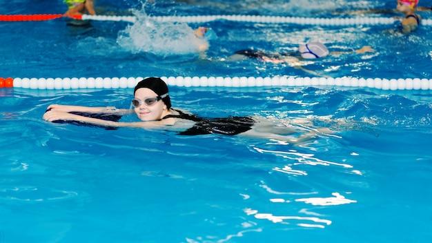 Cours de natation pour les enfants dans la piscine - belle fille à la peau claire nage dans l'eau