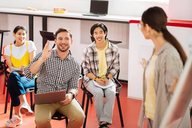 Cours passionnant. joyeux étudiant émotionnel assis avec son groupe et souriant tout en levant la main et en regardant l'enseignant professionnel
