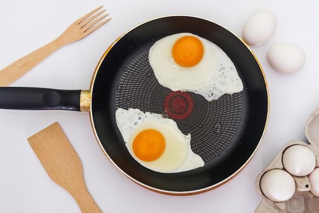 En cours de préparation du petit-déjeuner avec des œufs frais. œufs au plat de deux œufs dans une poêle.