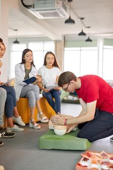 Cours de rcr avec de jeunes instructeurs de race blanche parlant et démontrant l'aide de premiers soins