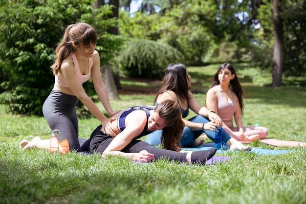Cours de yoga dans le parc. l'instructeur aide l'une des filles pendant que les autres se reposent. concept de santé et de bien-être.