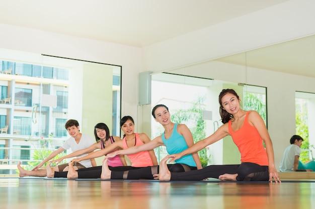 Cours de yoga dans la salle de studio, groupe de personnes faisant le côté assis étirer les bonnes positions