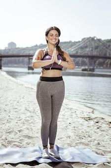 Cours de yoga. heureuse femme positive debout sur le tapis de yoga tout en mettant ses mains ensemble