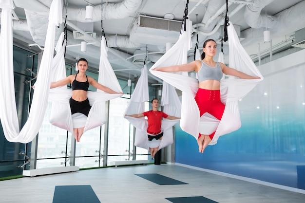 Cours de yoga volant homme et femme en forme et actifs se sentant calmes et libres tout en suivant un cours de yoga volant