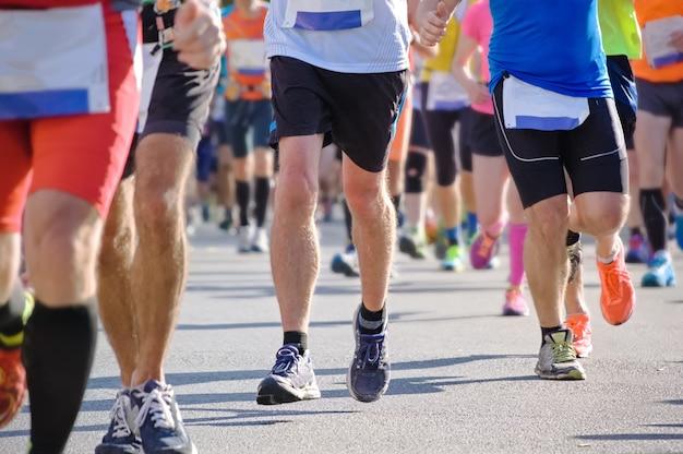 Course de marathon, pieds de nombreux coureurs sur route, compétition sportive, remise en forme et concept de mode de vie sain