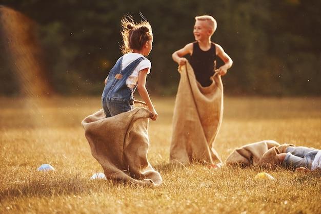 Course en sac de saut à l'extérieur sur le terrain. les enfants s'amusent pendant la journée ensoleillée.
