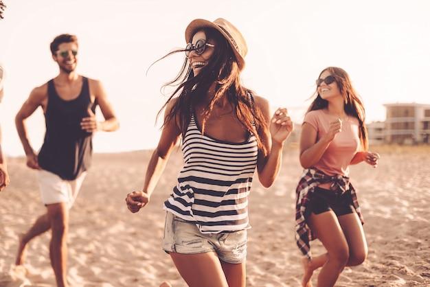 Course sans soucis. groupe de jeunes gens joyeux courant le long de la plage et ayant l'air heureux