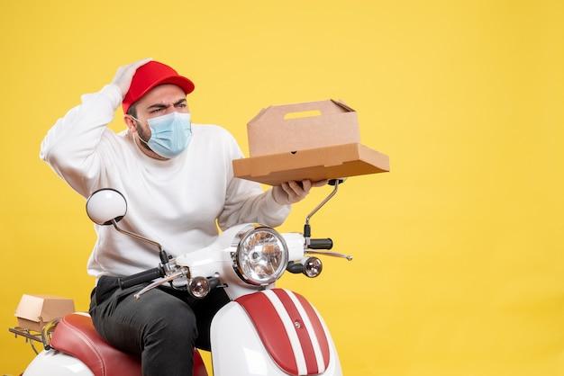 Coursier mâle en masque tenant de la nourriture de livraison sur jaune