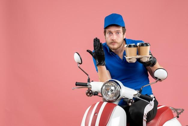 Coursier mâle vue de face assis sur un vélo et tenant des tasses à café sur le rose