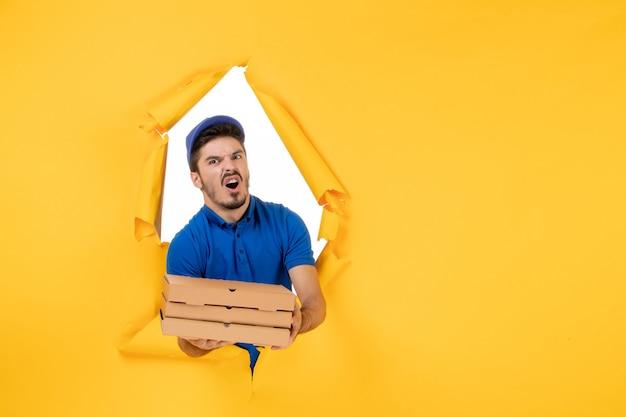 Coursier mâle vue de face tenant des boîtes à pizza sur un espace jaune