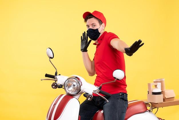 Coursier mâle vue de face en uniforme rouge et masque sur jaune