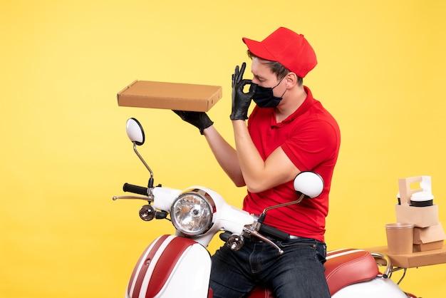 Coursier mâle vue de face à vélo en masque avec boîte de nourriture sur jaune
