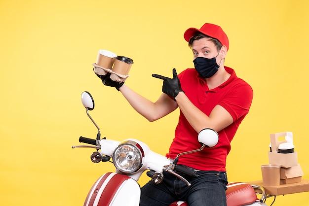 Coursier mâle vue de face à vélo en masque avec café sur jaune