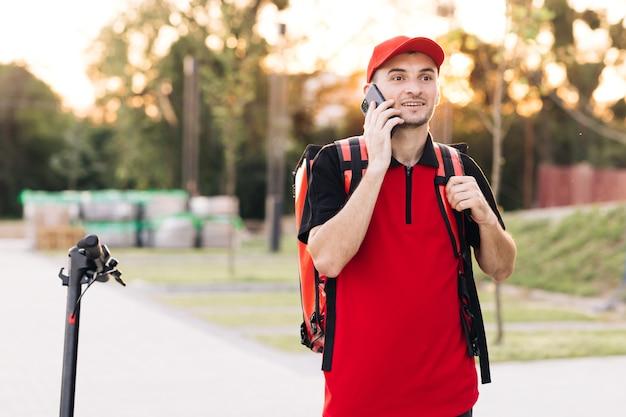 Un coursier masculin avec une boîte de nourriture isotherme arrive sur un scooter électrique à l'entrée