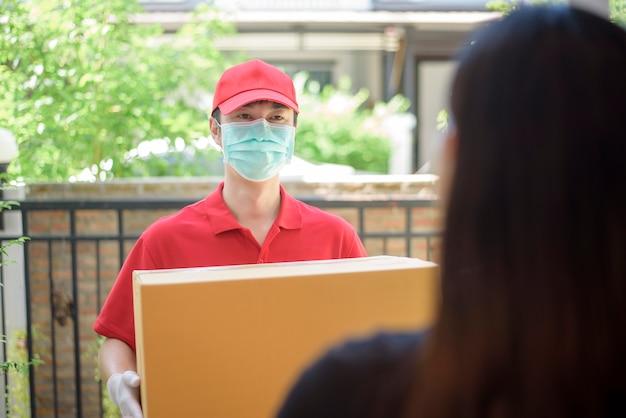 Le coursier, portant un masque et des gants de protection, livre une boîte de nourriture pendant l'épidémie de virus. livraison à domicile en toute sécurité.