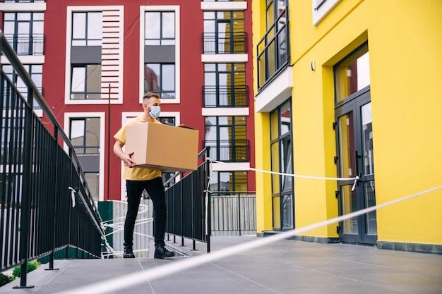 Un coursier portant un masque médical se dirige vers la porte avec une boîte en carton.