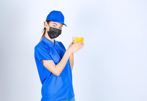 Coursière du restaurant en uniforme bleu et masque facial tenant un plat à emporter.