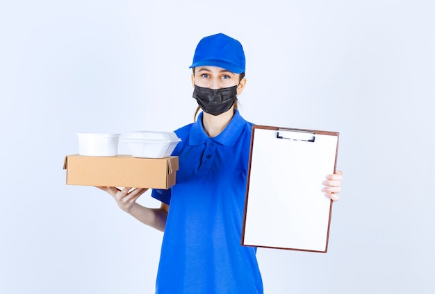 Coursière en masque et uniforme bleu tenant une boîte en carton, des colis à emporter et présentant la liste de contrôle pour signature.