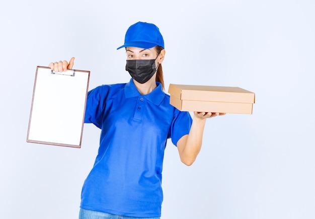 Coursière en uniforme bleu et masque facial livrant un colis en carton et demandant au client de signer sur le blanc.