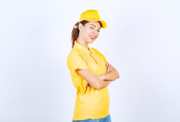 Coursière en uniforme jaune croisant les bras et donnant des poses professionnelles.