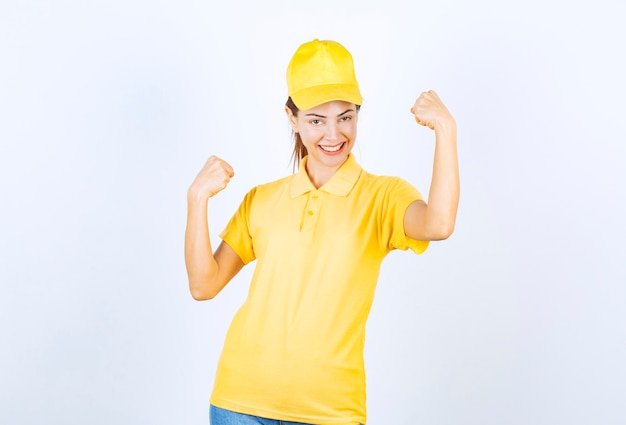 Coursière en uniforme jaune démontrant les muscles de ses bras.