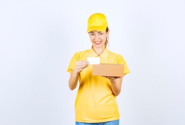 Coursière en uniforme jaune livrant un colis et offrant sa carte de visite.