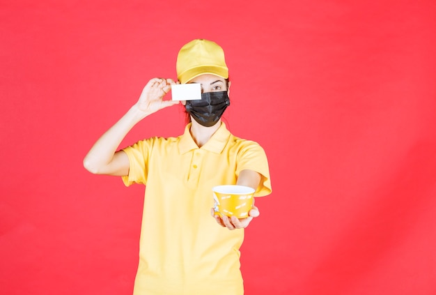 Une coursière en uniforme jaune et masque noir livre une tasse de nouilles et présente sa carte de visite