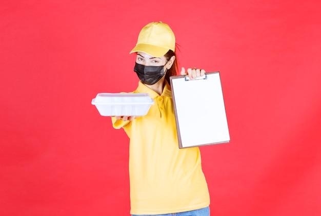 Coursière en uniforme jaune et masque noir tenant un colis à emporter et présentant la liste des signatures