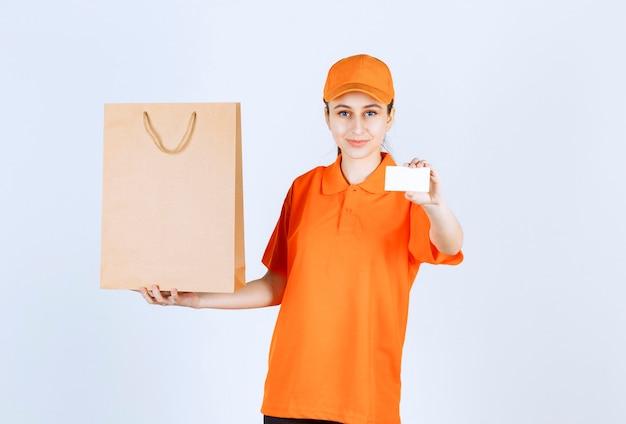 Coursière en uniforme orange livrant un sac à provisions et présentant sa carte de visite