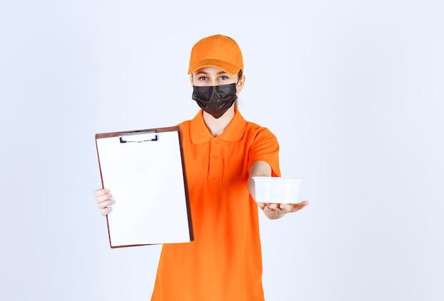Coursière en uniforme orange et masque noir tenant un gobelet en plastique et une liste de clients