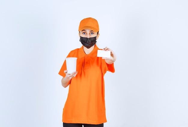 Coursière en uniforme orange et masque noir tenant une tasse à emporter en plastique et présentant sa carte de visite