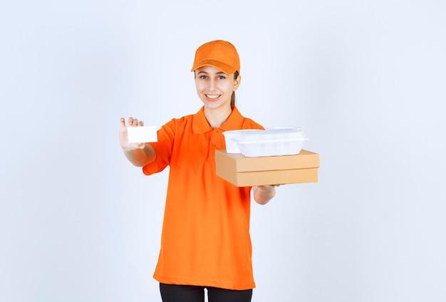 Coursière en uniforme orange tenant une boîte en carton et une boîte à emporter en plastique dessus tout en présentant sa carte de visite.