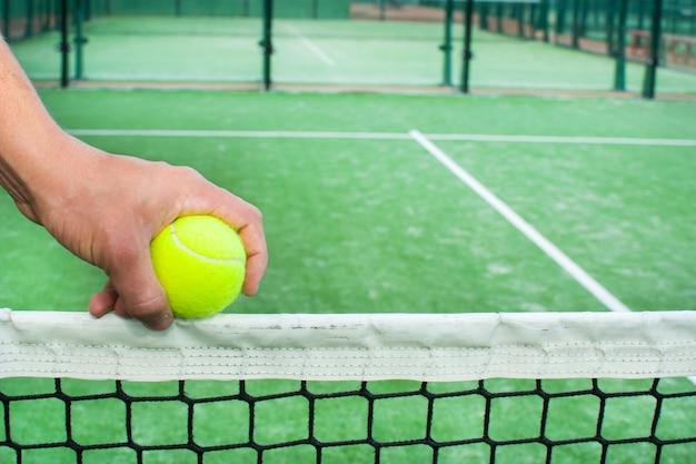 Court de tennis padel et main avec balle