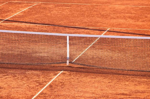 Court de tennis en terre battue vide et filet. prise de vue horizontale