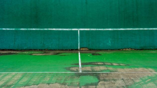 Court de tennis vert et mur pour la pratique