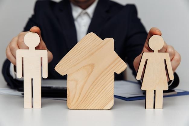 Courtier détient des figures en bois de l'achat de la jeune famille du concept de maison