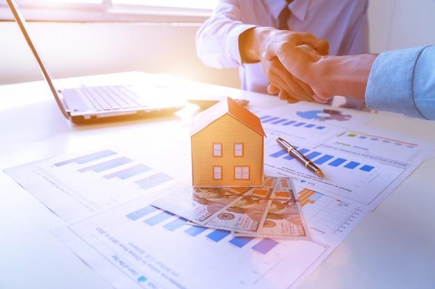 Courtier immobilier et client se serrant la main après la signature d'un contrat.