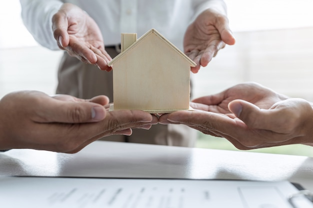 Courtier immobilier faisant signer le formulaire d'assurance et envoyant le modèle de maison au client après approbation