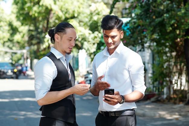 Courtiers financiers debout à l'extérieur et discutant des dernières mises à jour des réseaux d'information financière