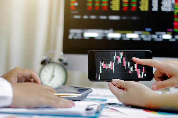 Courtiers en valeurs mobilières à la recherche de graphiques, index et nombres sur smartphone. les hommes d'affaires négocient des actions en ligne.