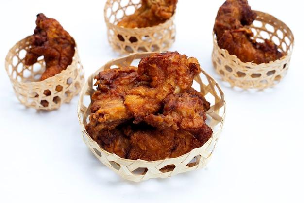 Cous de poulet frits dans un panier en bambou sur fond blanc.