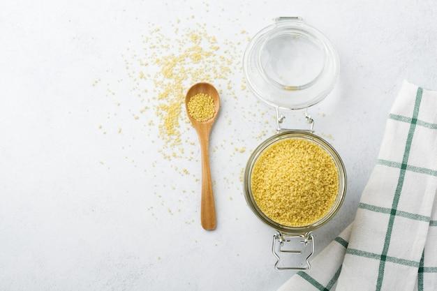 Couscous aux céréales de blé cru dans un bocal en verre sur un béton léger ou une pierre. cuisine traditionnelle d'afrique du nord et du sud de l'europe.