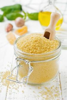 Couscous de céréales de blé brut dans un bocal en verre sur un fond de béton léger ou en pierre cuisine traditionnelle de l'afrique du nord et du sud de l'europe