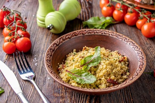 Couscous dans un bol avec de l'huile d'olive et des tomates séchées sur fond de bois, cuisine orientale, photo horizontale, gros plan